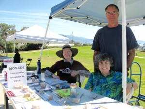 three people with registration materials on a desk in front of them and a green lawn behind